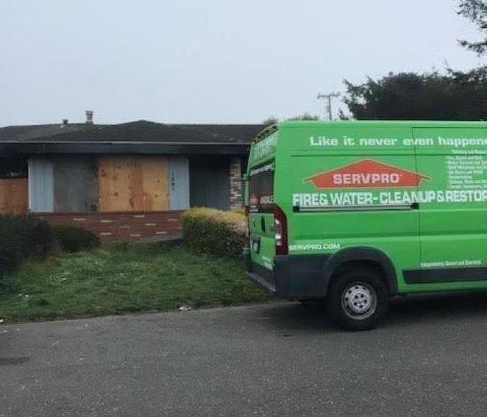 Picture shows SERVPRO van and house boarded up in background