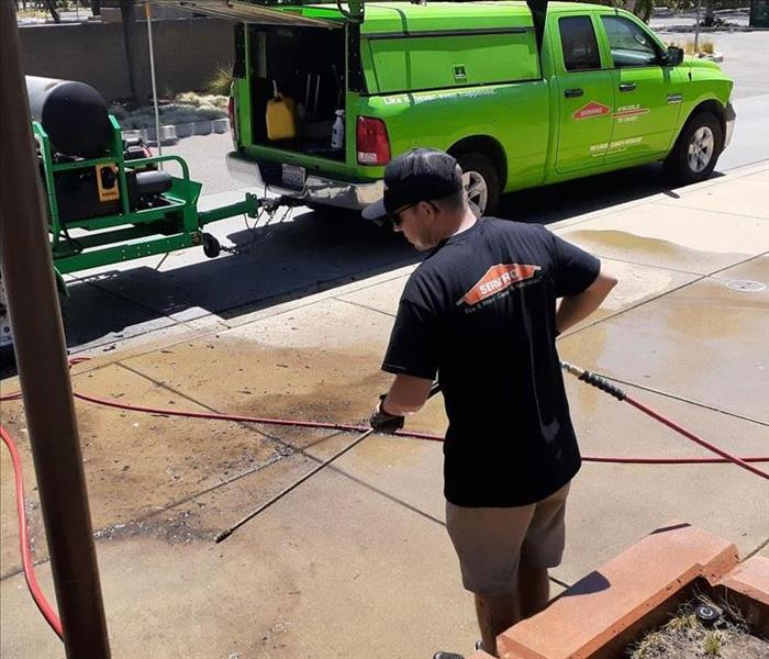 Pictures show a man power washing a sidewalk.